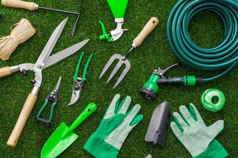 A pile of garden tools, water hose, and other working implements.