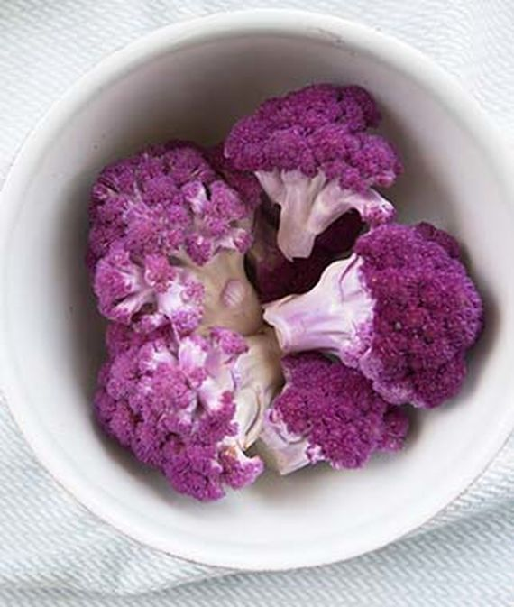 Top-down view of a Depurple Hybrid Cauliflower chopped up in a white, porcelain bowl.