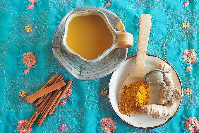 Top down of a cup of Krishna's Golden Turmeric Tea with the ingredients.