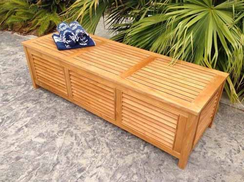 Oblique shot showing the outside of the Chic Teak Manhattan Deck Box with palm shrubs in the background.
