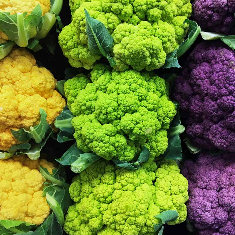 Orange, green, a purple cauliflower heads stacked in display case.