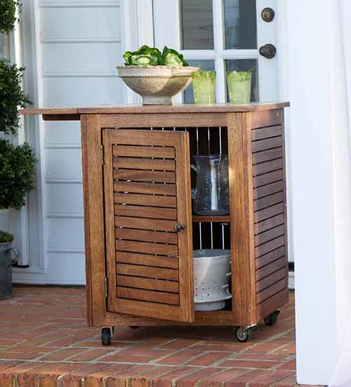 Small Lancaster Eucalyptus Wood Rolling Cart on a backyard patio.