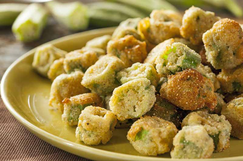 Closeup image of okra fried in a heavy cornmeal coating.