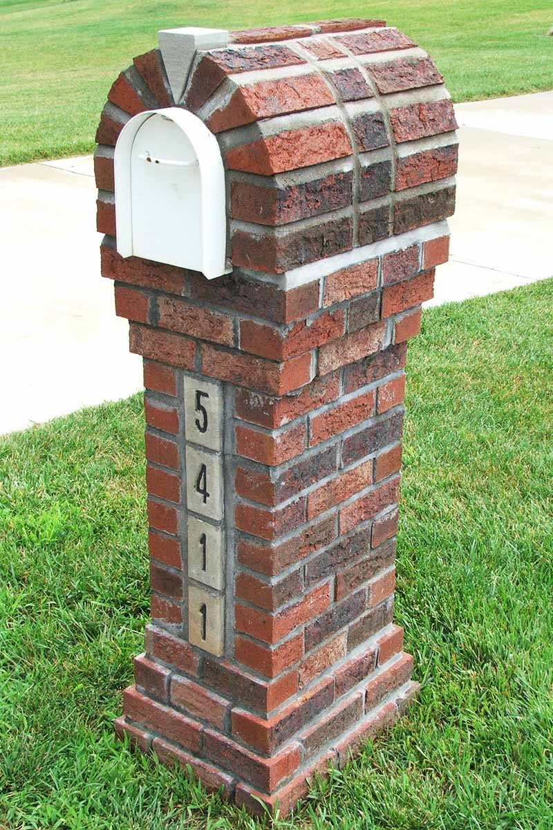 A brick and mortar mailbox cover built around a white metal box, with a house number on the front, installed in a green lawn beside a cement sidewalk.