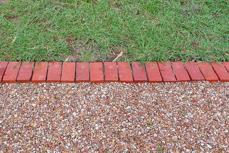 Horizontal image of two portions of a backyard, one landscaped with a green lawn and the other with a pebble pathway, divided horizontally with a border of brick blocks set into the soil.