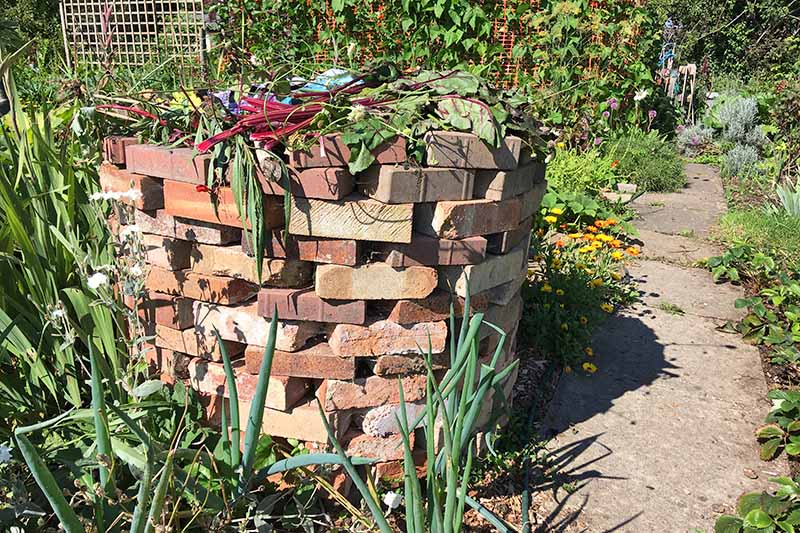 Horizontal image of builder's bricks stacked to make a compost container, loosely arranged without mortar to hold them in place, in a garden with a concrete path on a sunny day.