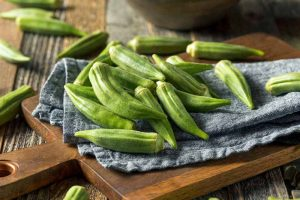 Freshly harvest okra on a blue kitchen towel on a small wooden cutting board.