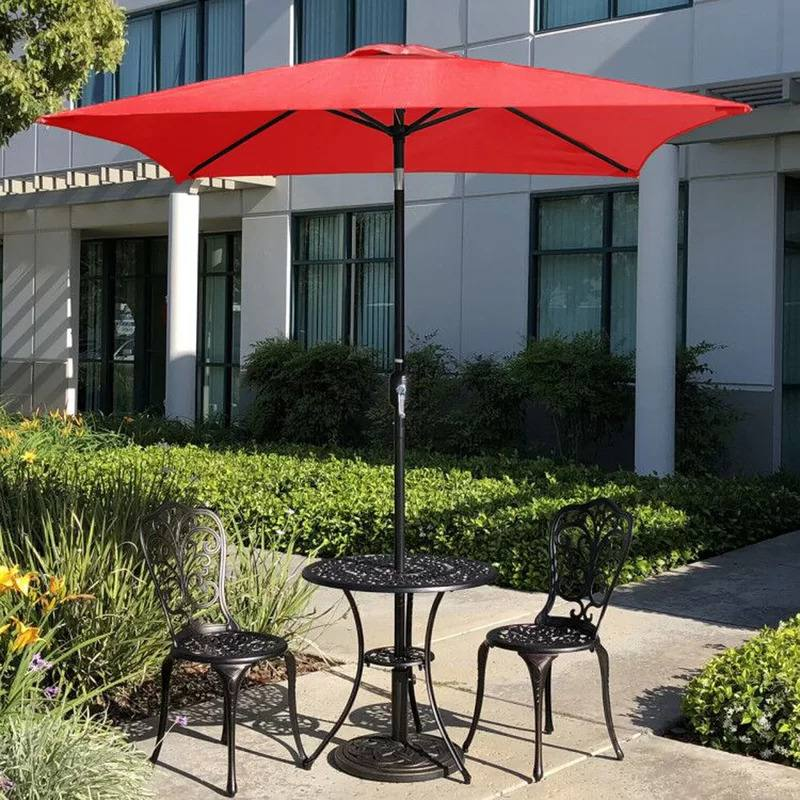 A red colored Bradford Patio 6.5' Square Market Umbrella attached to a small wrought iron table with two chairs in backyard setting.