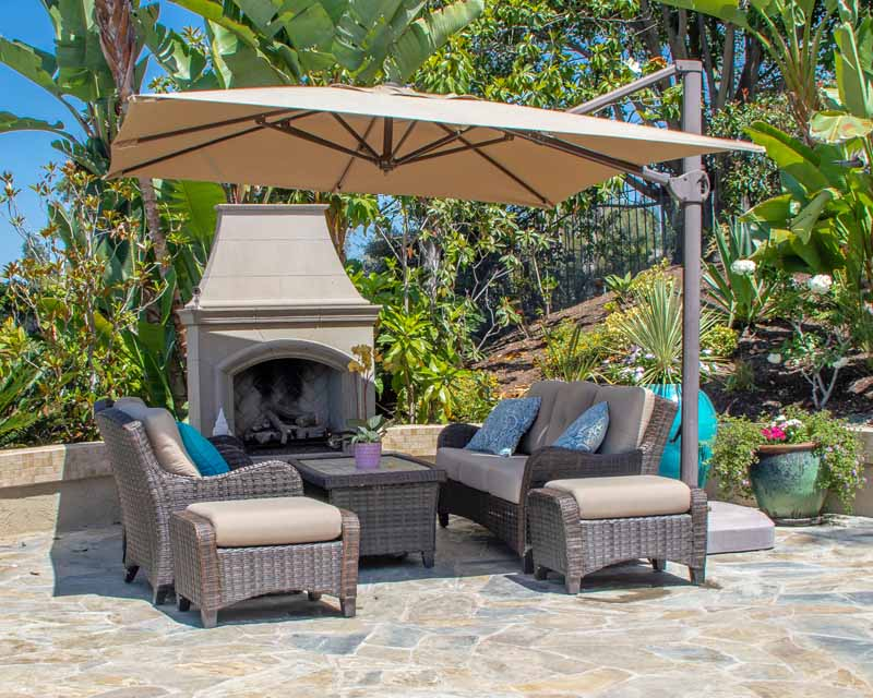An outdoor fire place with an outdoor furniture set along with a cantilever or offset patio umbrella.