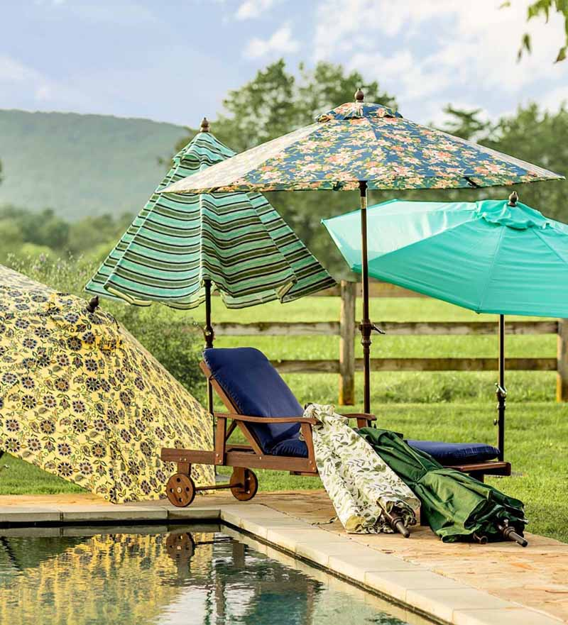 Multiple colors and styles of the Plow & Hearth Classic Patio Market Umbrella set up next to a high end pool in a rural backyard.