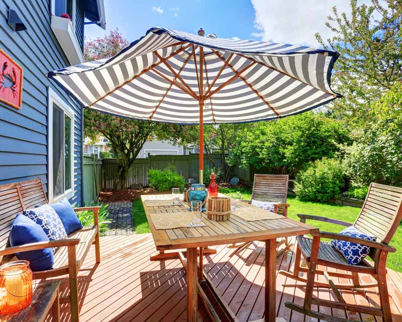 A striped market style umbrella on the back deck of a typical suburban home.
