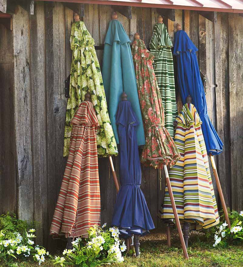 Plow and Earth Classic Market Umbrellas in various styles and colors, folded and leading up against a rustic wooden fence.