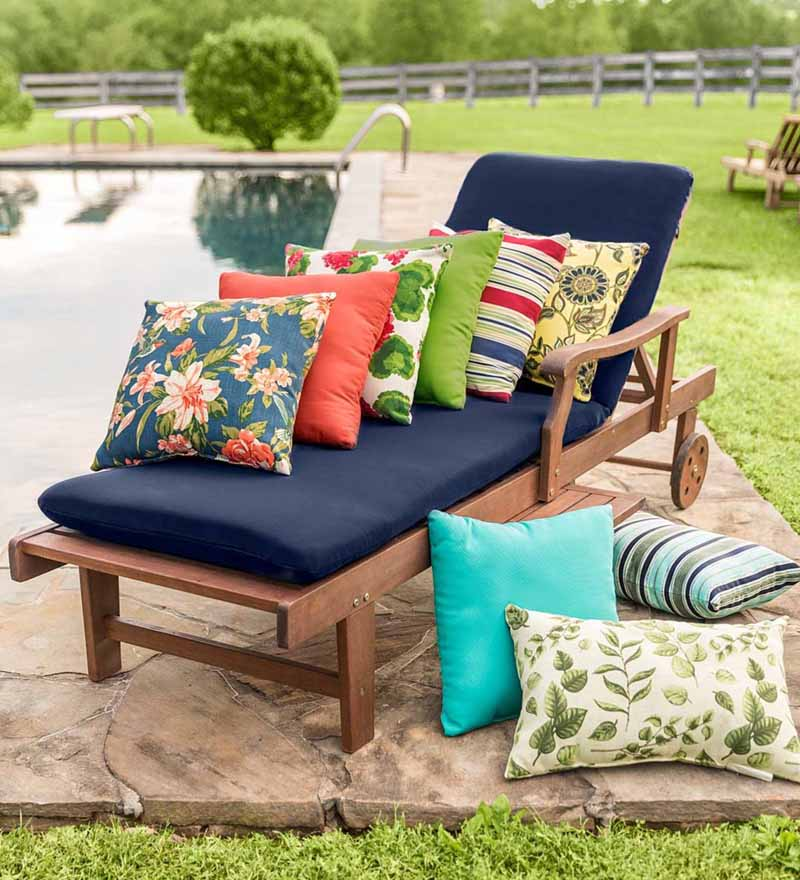 Different colors and patterns of the Plow and Hearth Polyester Classic Throw Pillows on a lounger next to a pool.