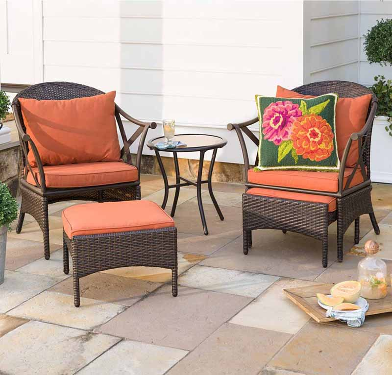 Wicker Patio Furniture Set with Cushions on a stone patio.