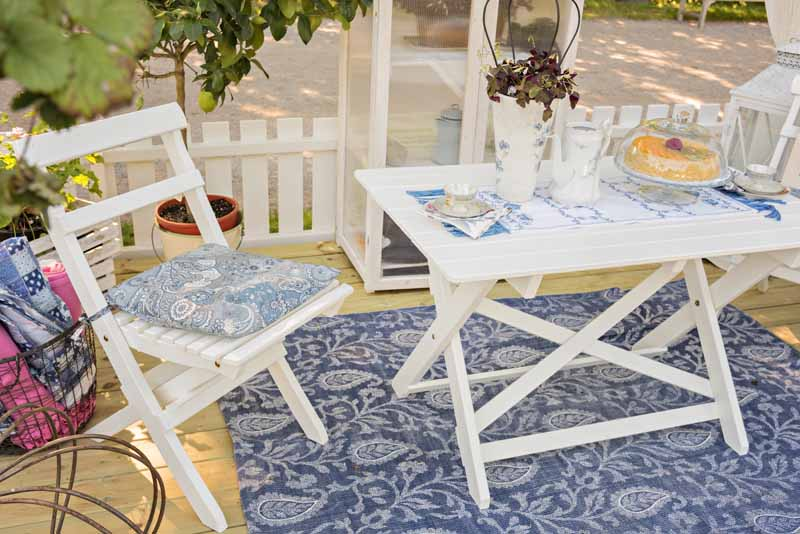 White wooden patio chairs and table sit on a blue patterned outside rug.