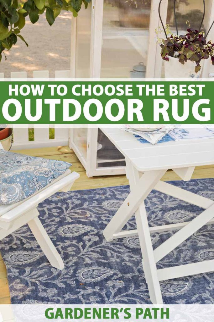 An outdoor blue area rug with white wooden patio furniture.