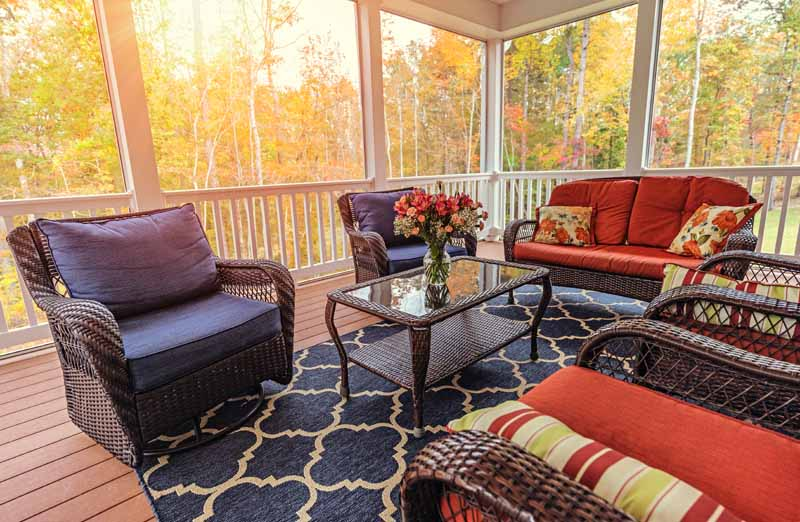 A covered porch in the spring time with red cushioned brown wicker furniture and a large blue outdoor rug.