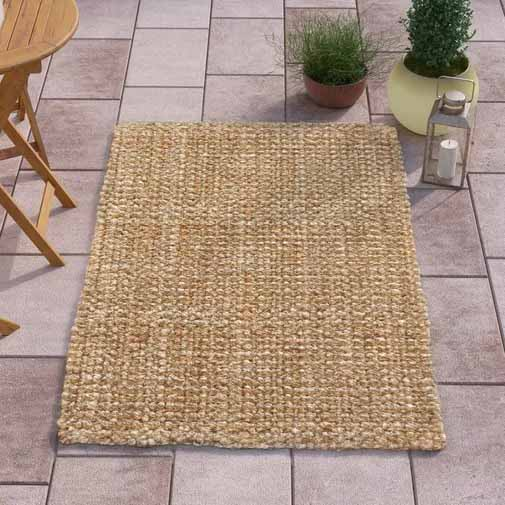 Highland Dunes Ellyson Brown Indoor/Outdoor Area Rug on a square stone patio.