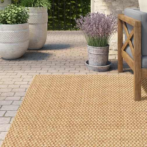 Orris Sand Indoor-Outdoor Area Rug on a outside paver patio.