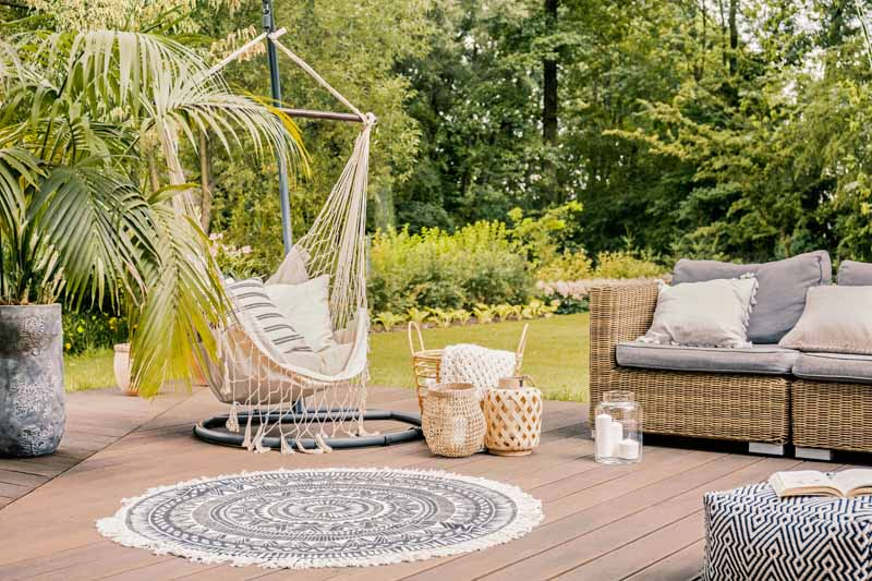An uncovered wooden deck with a hammock, wicker couch, and blue circular outdoor carpet.