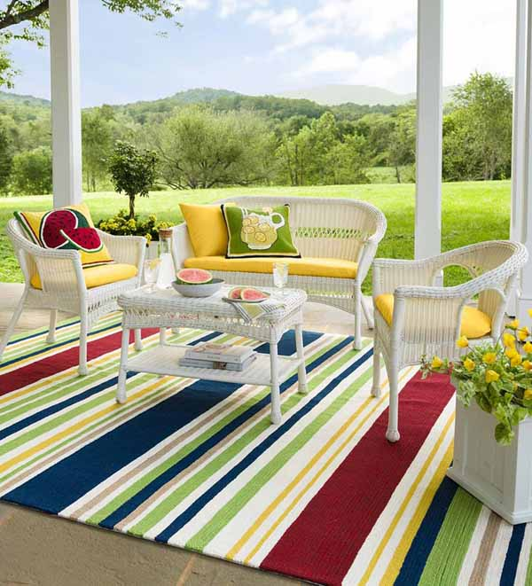 Plow and Earth outdoor rainbow rug on a covered porch with white wicker furniture.