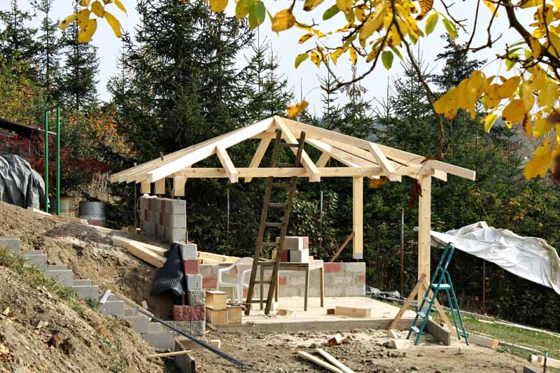 A custom garden gazebo being constructed in a terraced lawn.