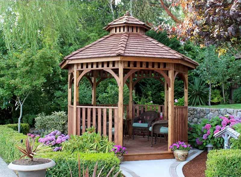 Bayside 10 Ft. W x 10 Ft. D Cedar Patio Gazebo in a garden setting with landscaped woody shrubs and flowering perennials.