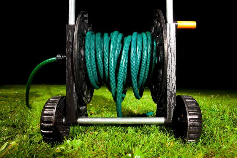 A mobile garden hose cart on lush green grass.