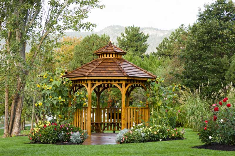 A wooden gazebo made of cedar in a park-like setting.