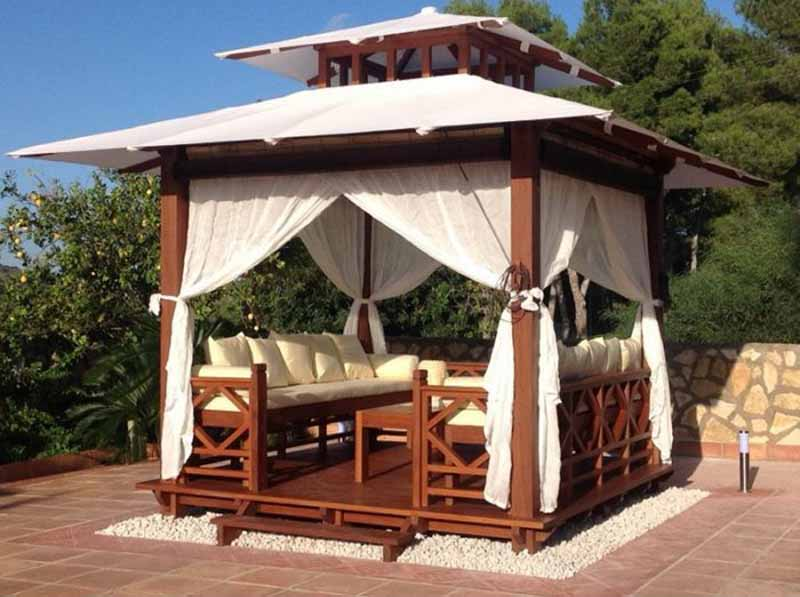 Exaco Bali 10 x 10 ft. Gazebo Retreat set up in on a stone patio and establishing an outdoor room.