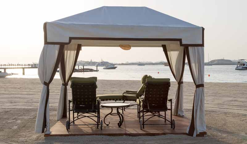 A gazebo constructed from aluminum supports with a fabric covering. Beach setting with ocean ships in the background.