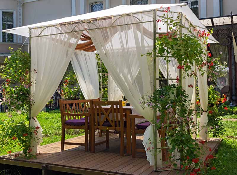 A soft topped gazebo with fabric curtains in a residential courtyard garden.