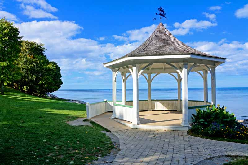 A white wooden gazebo overlooks a large lake. Blue skies with white, puffy clouds are in the background.