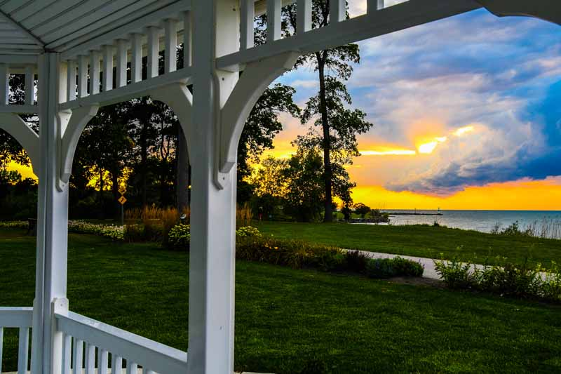 A sunset view from inside a white-painted gazebo overlooking a sunset.