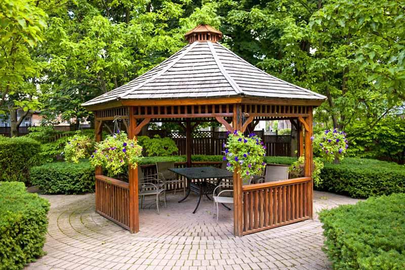 Wooden hexagonal gazebo in landscaped garden with interlocking stone patio.