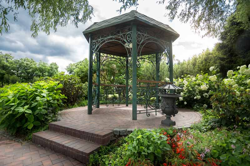 An intricate gazebo manufactured from aluminum in a park-like residential garden.