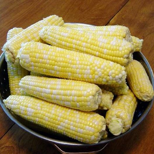 Ambrosia hybrid sweet corn cobs on a platter.