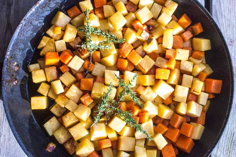 Overhead horizontal image of a cast iron pan filled with large diced rutabaga and other root vegetables, topped with sprigs of thyme, on an unfinished wood table.