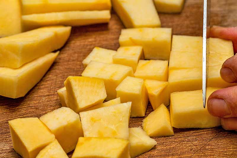 Horizontal closeup image of pieces of yellow-fleshed peeled rutabaga being chopped on a wooden cutting board, with a hand holding several pieces steady at the right of the frame and chopping with a knife.