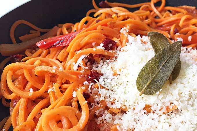 A nest of spiralized sweet potato noodles with roasted red peppers and sauce, topped with grated cheese and two fried sage leaves, in a black nonstick frying pan.