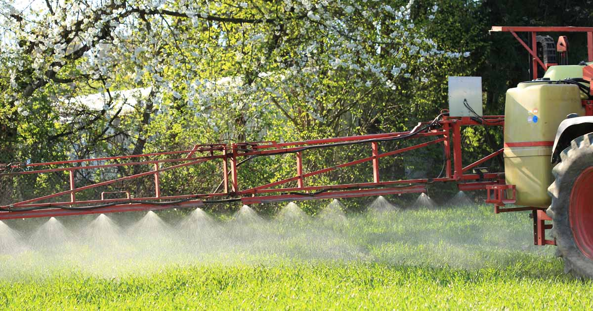 A tractor sprays a biofungicide with a sprayer boom and tanks.