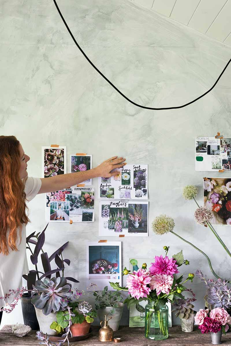Vertical image of Clare Nolan pointing to images taped up on a gray wall, with various flower arrangements and plants in containers.