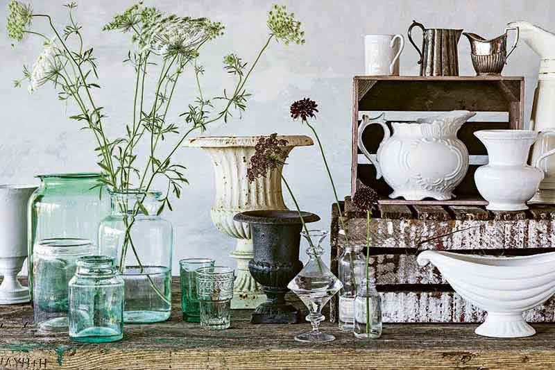 Horizontal image of various vases and containers for arranging flowers, made of glass, ceramic, and other materials, with a small brown shelf to the right, against a light gray backdrop with Queen Anne's lace in a container of water, on a wood surface.