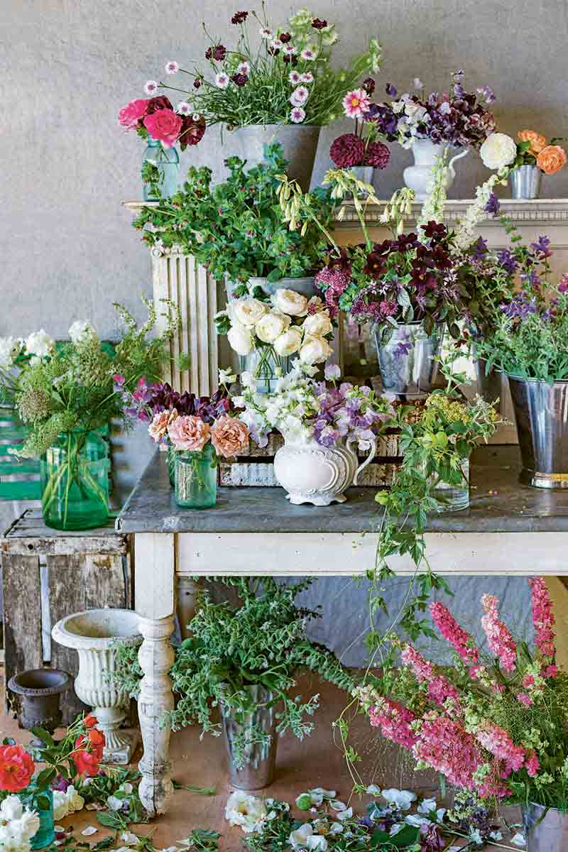 Vertical image of many flower arrangements in vases and other types of containers, on a wooden desk, with more pots and cut flowers artfully arranged on the floor, against a beige wall.