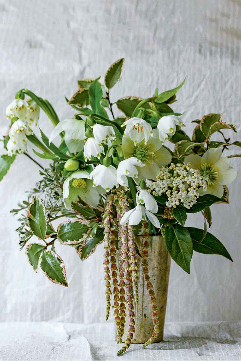 Vertical image of an arrangement of white flowers and foliage with an ornamental spiller in the front, on a white surface against a gray wall.
