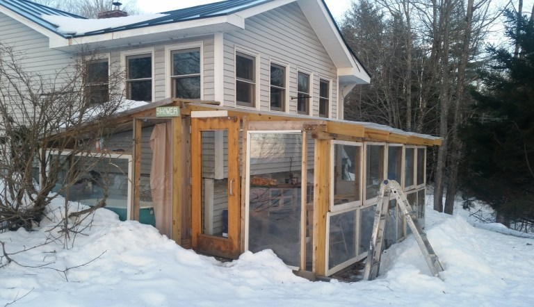 A DIY lean-to greenhouse built onto the backside of a home.