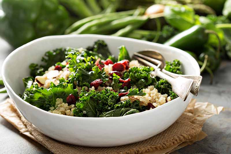 A white bowl containing a beautiful salad of raw Brassica oleracea and quinoa, with a spoon and fork in the side. Under the bowl is a piece of hessian and brown paper, on a gray surface. In the background, various green vegetables in soft focus.