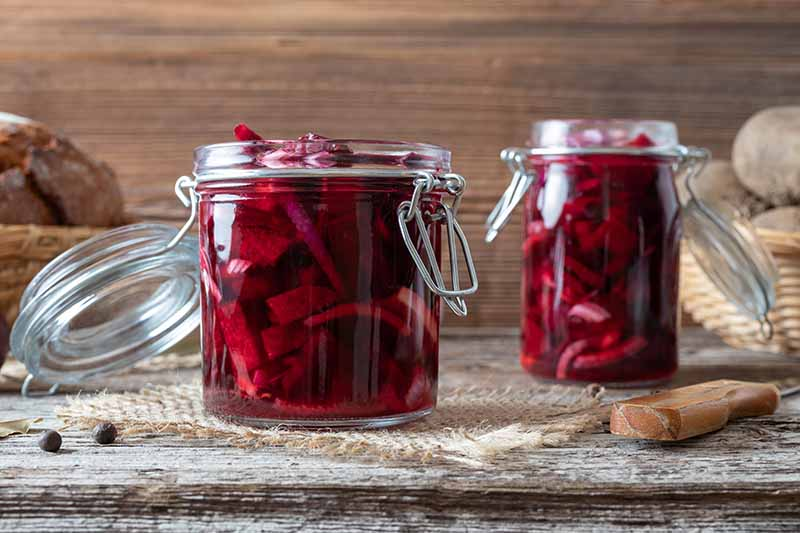 A close up of two jars containing slice beets in liquid, the red color contrasting with the rustic wooden background of a woven mat on an outdoor table with a wicker basket to the right of the frame.