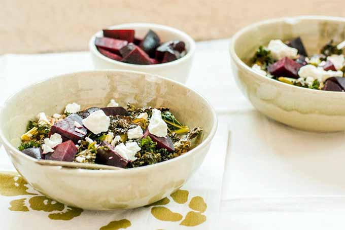 Two bowls of coconut, ginger, kale, goats cheese and beets, on a white and gold fabric placemat. Behind is a small white bowl with beetroot slices. The background is a white table cloth.