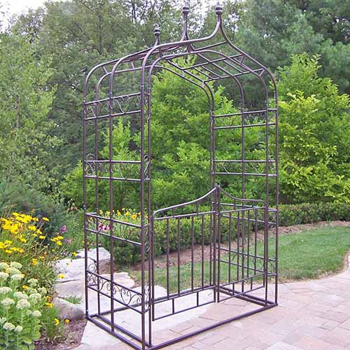 A metal arbor with ornate wrought iron work and gates, shown on a brick path with a background of trees and bushes.